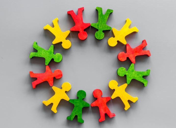A set of wooden people figures coloured in yellow, red and green, arranged in a circle on a grey desk.