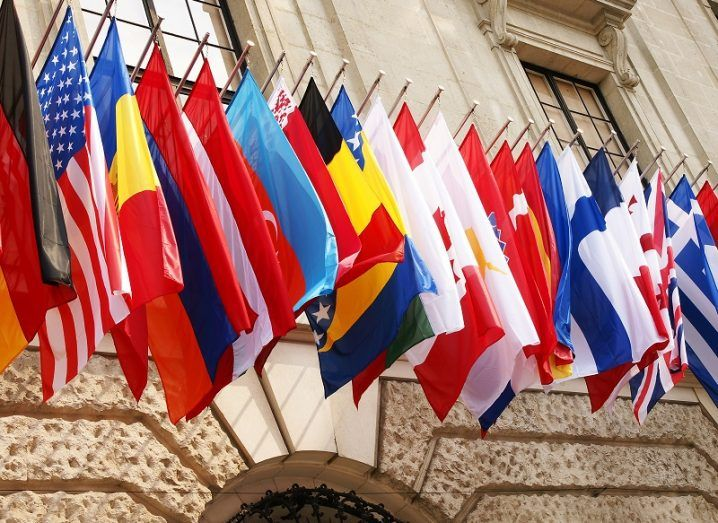Flags of OECD members in a row outside a beige-brick building.