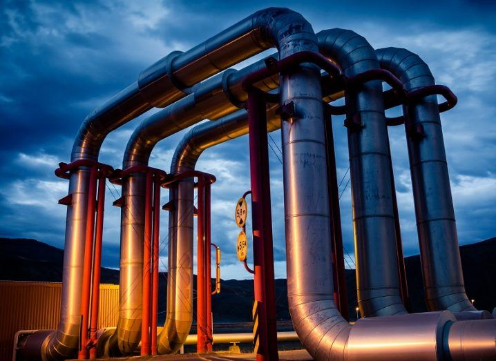 Three large pipes as part of a geothermal energy network against a dusk sky.