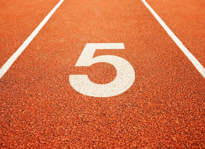 The number five painted in white onto an orange running track.