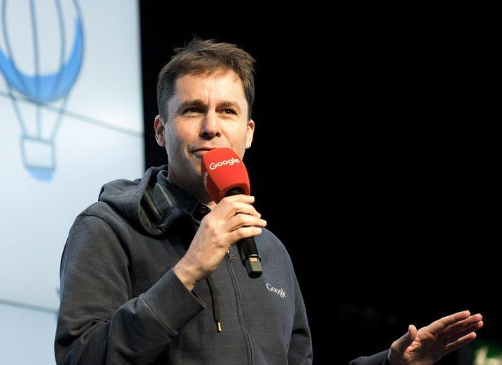 Nick Leeder holding a red microphone on stage at a Google event.