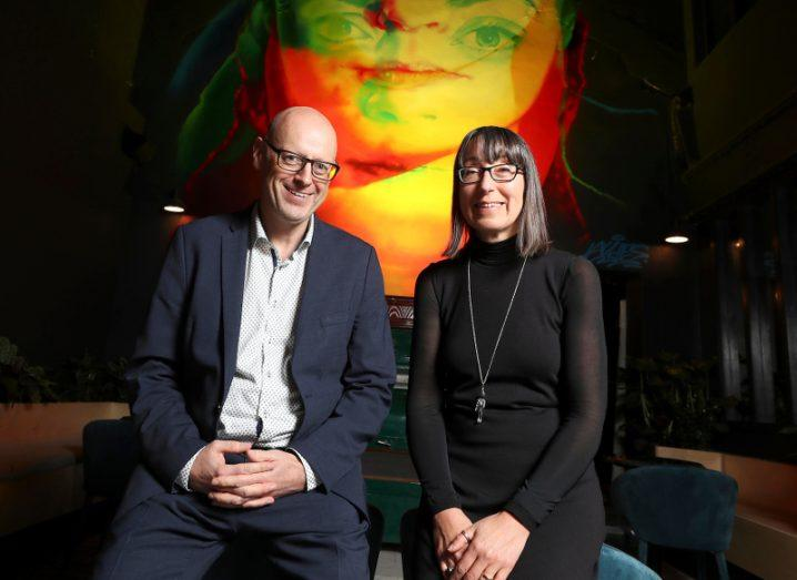 A smiling man and woman sit with arms in their laps, photographed against a wall adorned with artwork of a woman's face.