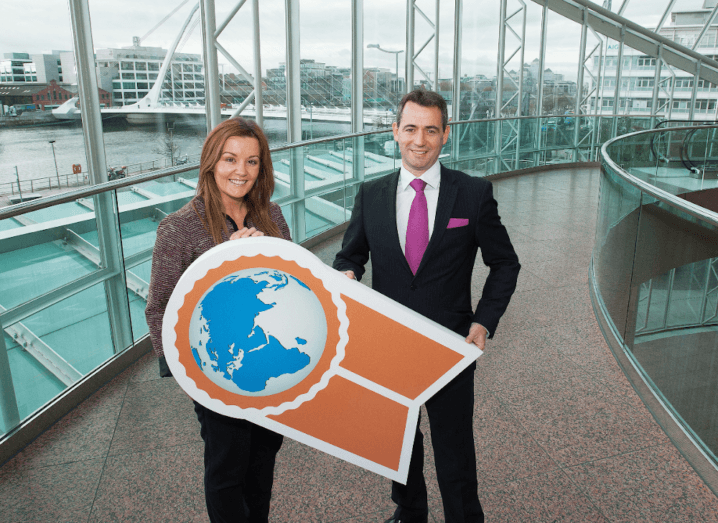 A woman and a man holding a sign together inside the Dublin Convention Centre.