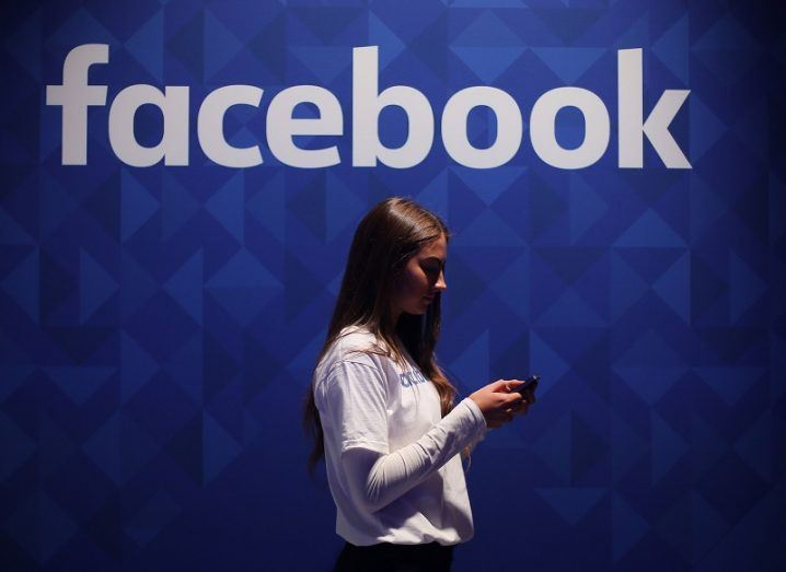 Woman on her phone in front of the Facebook logo on a blue wall.