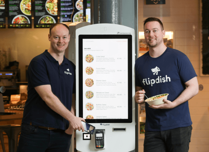 Two men standing on either side of a white kiosk with a touch screen for ordering food. They are both wearing navy T-shirts that say 'Flipdish'.