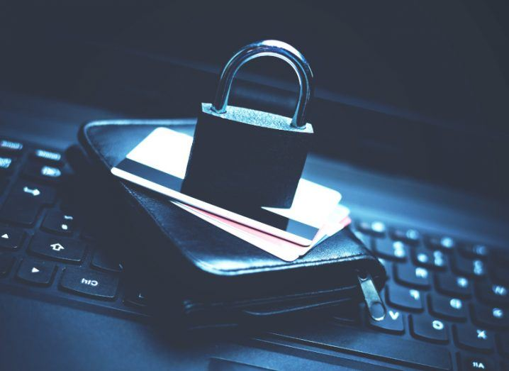 A padlock sits on top of a credit card, on top of a wallet, on top of a keyboard, representing fraud detection.