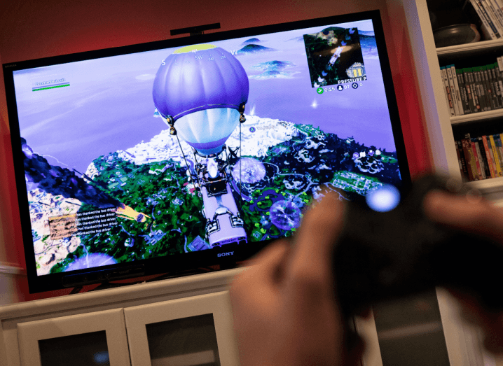 A person gaming on Fortnite. A PlayStation controller is out of focus and Fortnite is displayed on the TV screen.