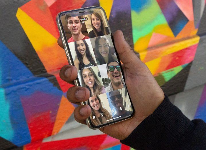 Hand holding a phone with the Houseparty app open against a background of a multicoloured wall.