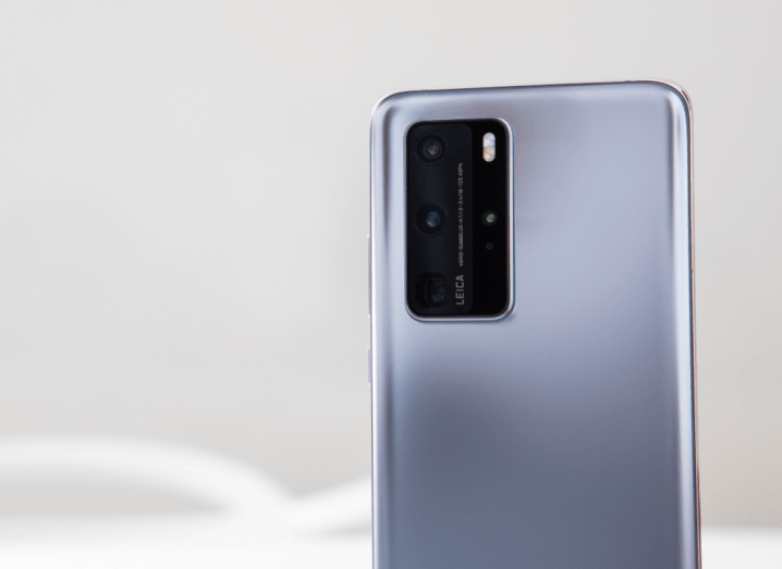 The back of the Huawei P40 Pro phone, which is a silver device with a glass back. There is a large black camera module with three camera lenses and two flash lights.