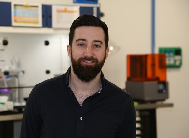 Seán McConnell in a black shirt smiling in his lab that includes a 3D printer.