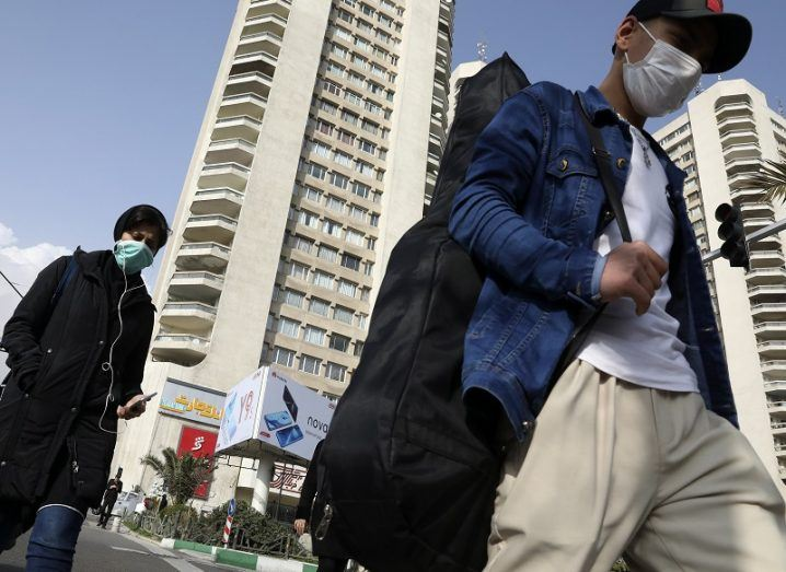 Pedestrians wearing face masks crossing a street in northern Tehran, Iran.