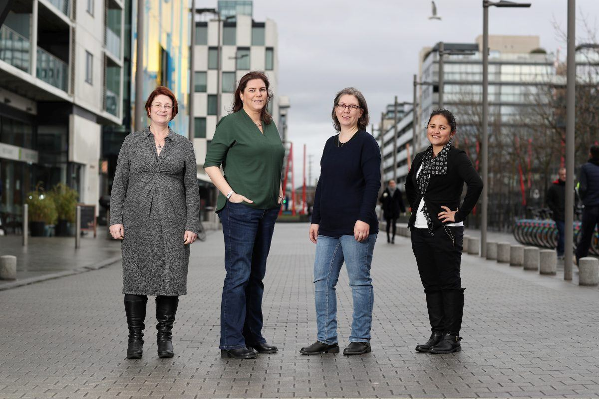 Four women of varying ages stand in a row smiling on a quiet Dublin street. They all work in high-end computing at the ICHEC.