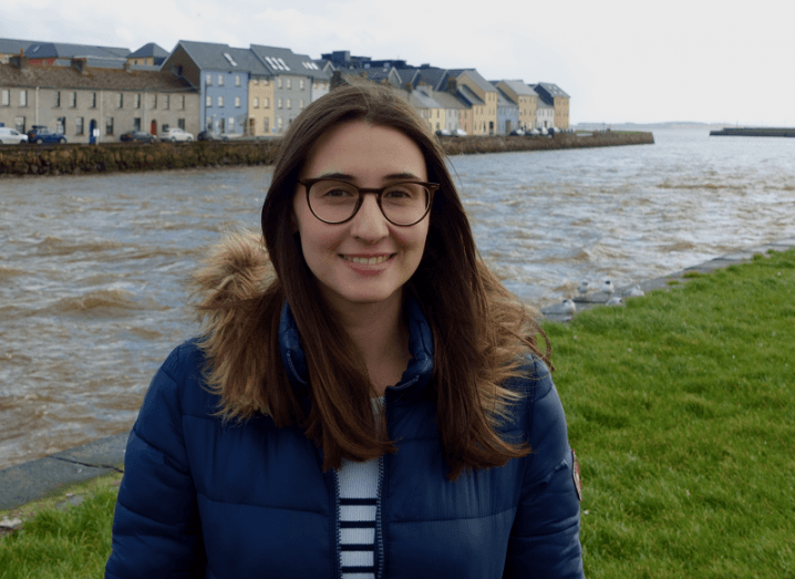 Joana Barros smiling in a blue jacket and glasses, standing in front of a body of water and houses.