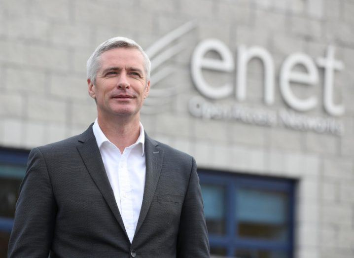 A man in a black suit stands in front of a building that says 'Enet'.