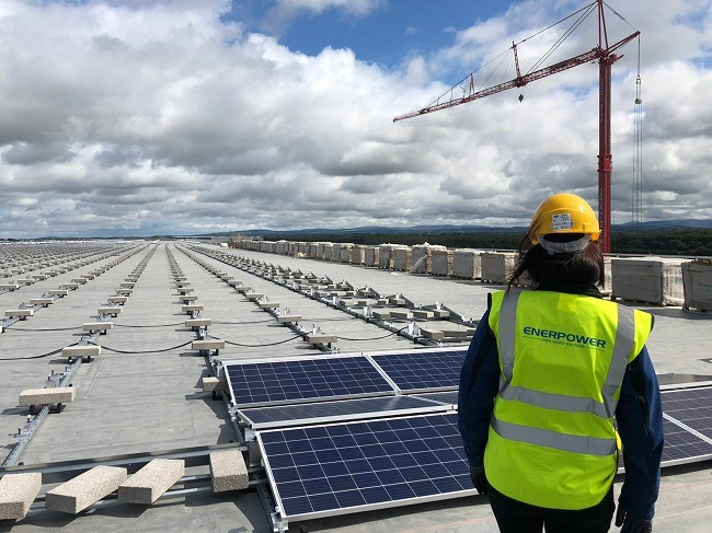 Shot of Brigid Walsh from behind wearing a hi-viz jacket and hard hat during the installation of solar panels on the Lidl roof with a crane and sky in the background.