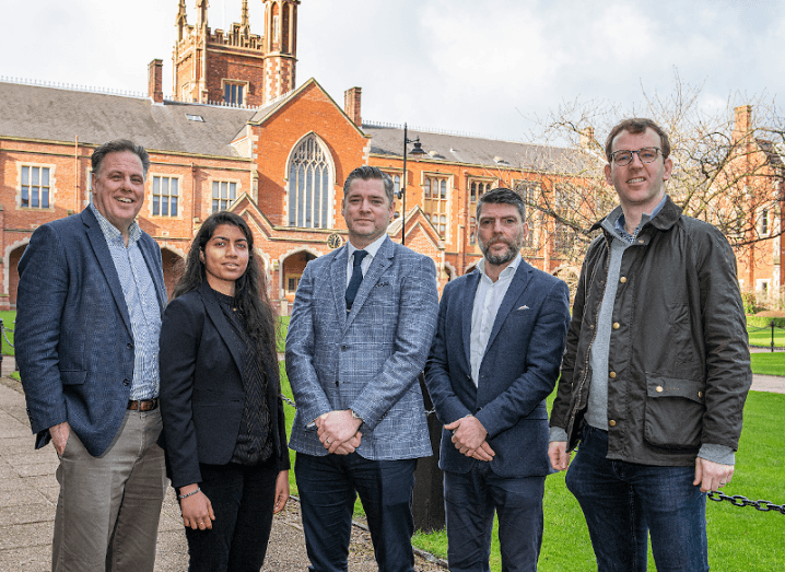 A group of five people standing outside a red-brick building at Queen's University Belfast.