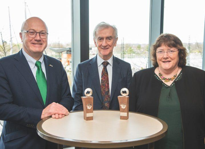 Prof Mark Ferguson, Prof Neville J Hogan and Dr Ann B Kelleher standing at a table with two awards.
