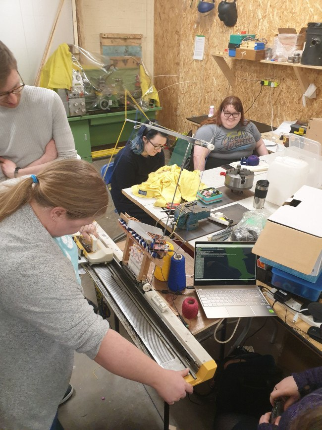 A group of young men and women are gathered around a messy workbench, creating a 'Twitter Knitter'.