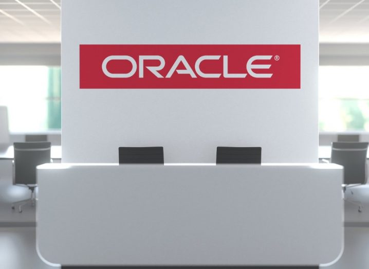 Logo of Oracle on a wall in a white, modern office.