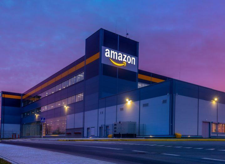 A large building with the 'Amazon' logo alight at the top, against a darkening sky at sunset.