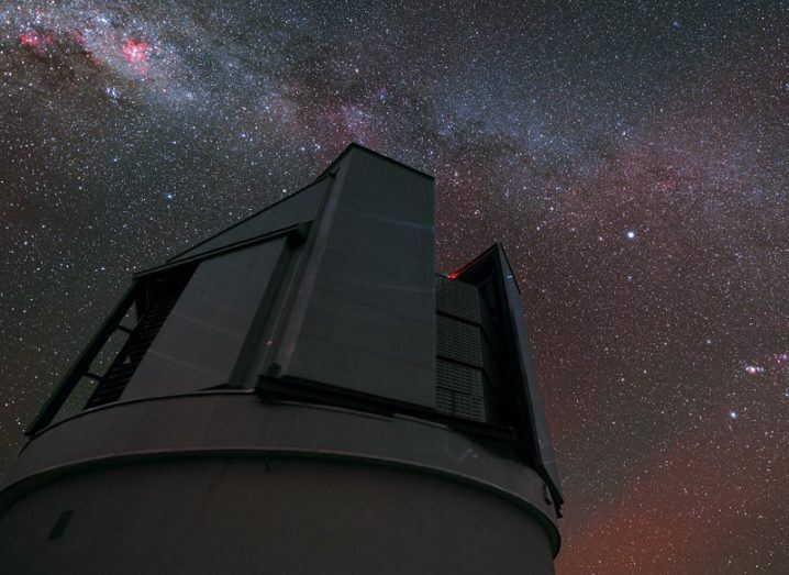 Looking upwards at a large telescope below a colourful night's sky.