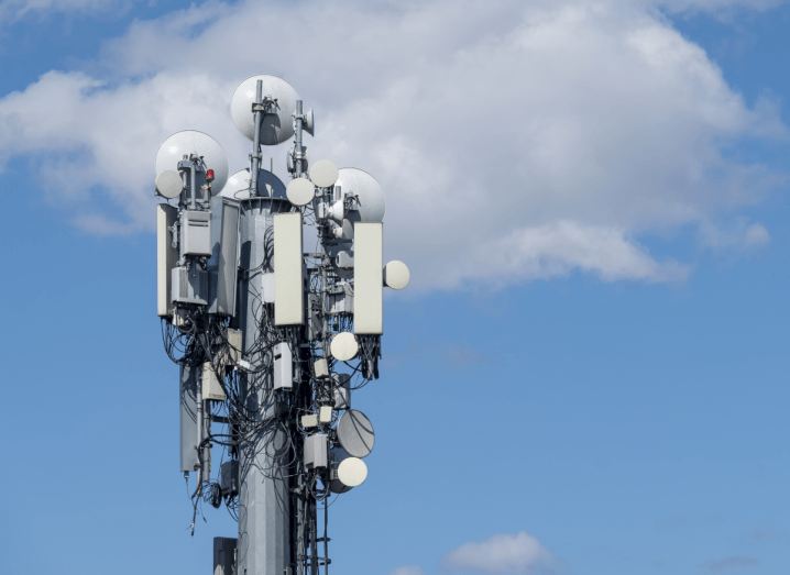 A cellular base station in front of a cloudy blue sky.