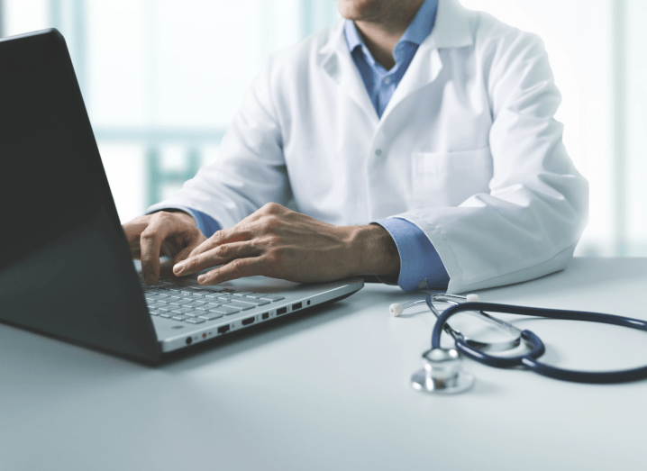 A doctor in a white coat using a laptop.