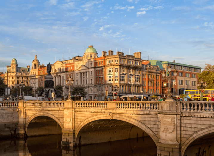 A scenic view of Dublin at O'Connell Bridge. The sky is blue and the River Liffey is in the foreground.