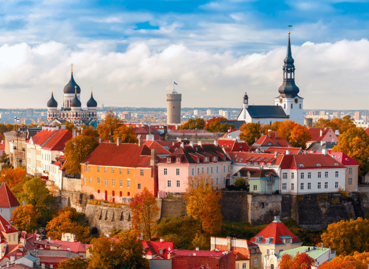 The skyline of Estonia's capital city, Tallinn. There are many buildings with red tile rooves and there are colourful autumn leaves.