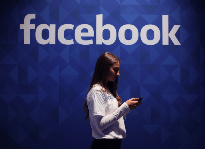A woman in a white T-shirt and long-sleeved shirt stands in front of a blue wall with the Facebook logo on it, holding a smartphone.