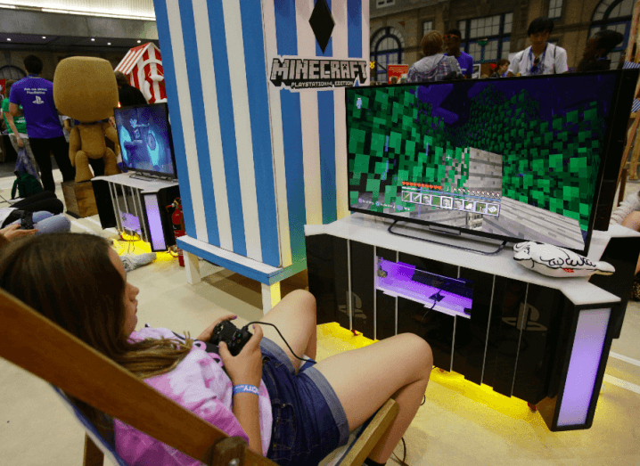 A young child sits on a chair playing Minecraft at a public gaming event.