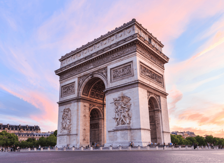 The Arc de Triomphe monument in France at dusk. It is a large white arch.