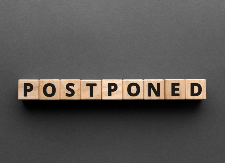 Wooden blocks spelling out the word 'postponed'.