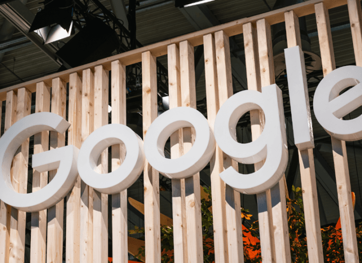 A white Google logo against a background of wooden slats.