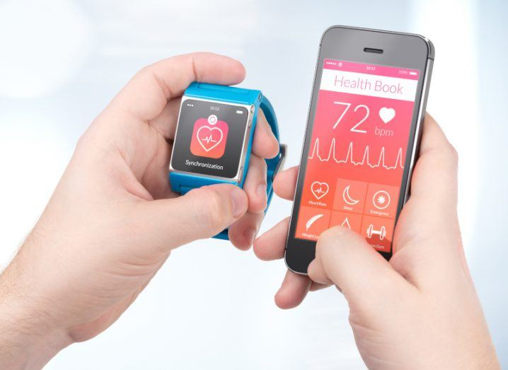 Someone holding a mobile and smart watch, showing various health stats.