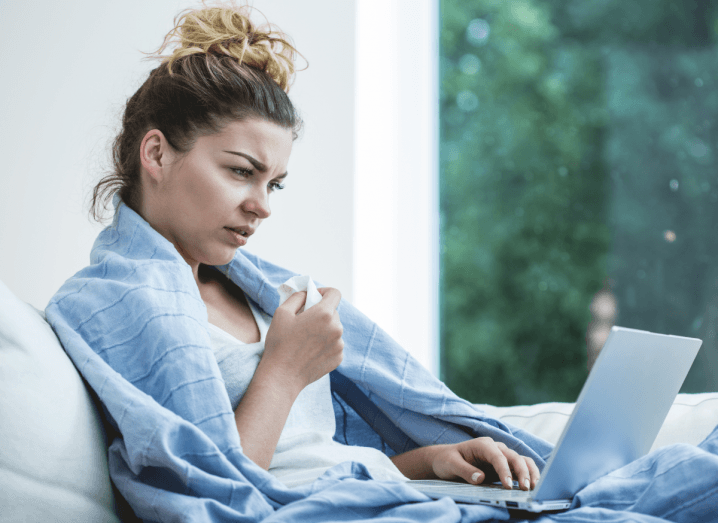 A sick woman using a laptop while wrapped in a blue blanket.