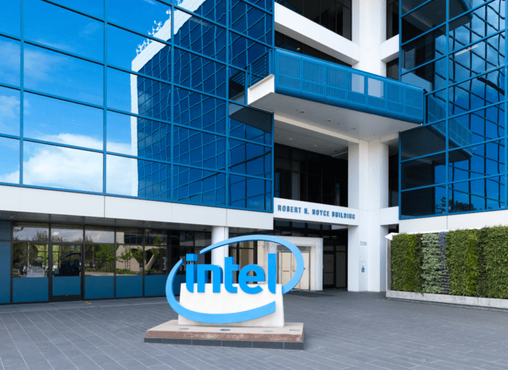 The Intel logo displayed out of a large, glass-fronted office building in Santa Clara, California. To the right of the sign there are hedges. From the reflection in the building, a sunny, blue sky is visible.