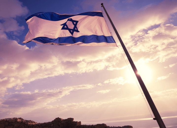 The flag of Israel waving in front of a blue sky with clouds.