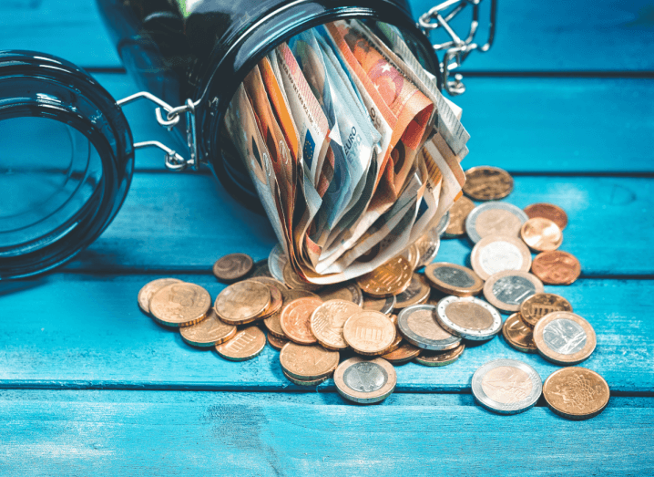 A jar of money poured over on a blue wooden surface.