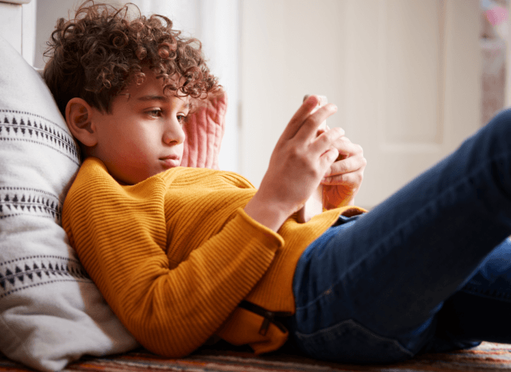 A child playing a mobile game while sitting on a sofa. He is wearing a yellow jumper and blue jeans and has curly brown hair.