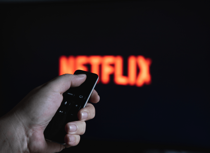 The Netflix logo displayed on a screen in the background behind a viewer holding an Apple TV remote.