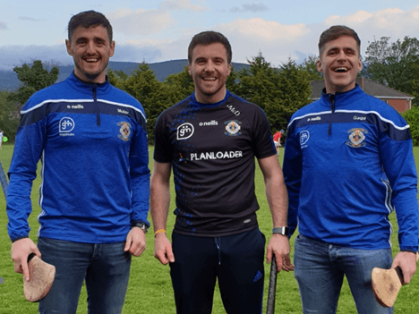 Three men standing in a field holding hurls and smiling, wearing Ballyboden hurling gear.