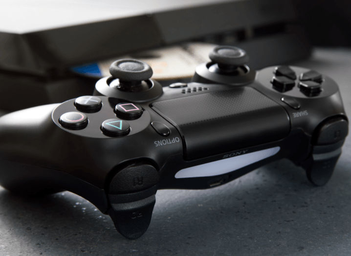 A black PlayStation 4 controller and console on a surface.