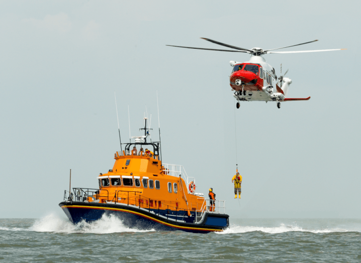 An orange boat underneath a helicopter that is dropping a person onto the boat. Both vehicles are in the sea under a grey sky.