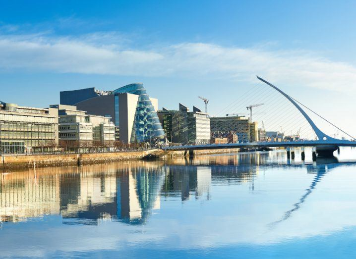 A bright skyline view of Dublin City, with a calm River Liffey in the foreground and the Samuel Beckett Bridge is in the background.
