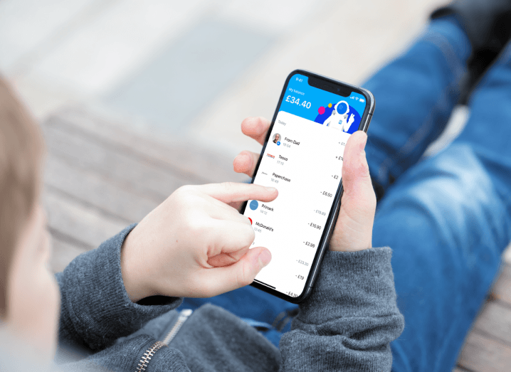 A child using an iPhone to manage their money on Revolut Junior.