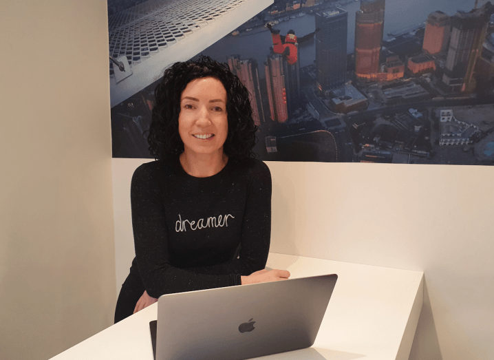 A woman with black, curly hair stands beside a MacBook, wearing a black shirt.