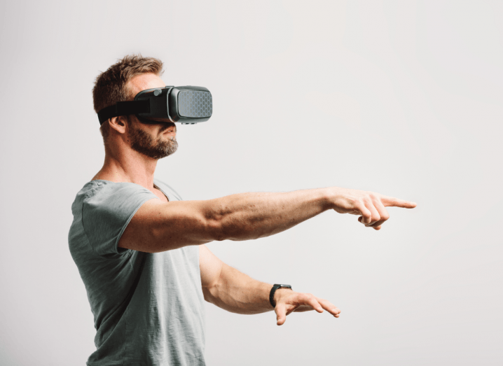 A man wearing a VR headset and a grey T-shirt stands in front of a white background with his right arm pointed away from his body.