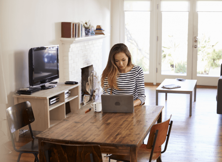 A woman using a laptop at a table in her kitchen, doing work from home.