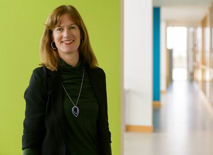Dr Lisa Ryan smiling in a dark green cardigan against a bright green wall in a long corridor.
